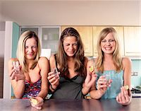 Three Teenage Girls Sit at a Kitchen Counter Grimacing After Drinking a Shot of Tequila Stock Photo - Premium Royalty-Freenull, Code: 6106-07008083