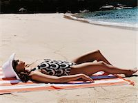 slim - Young Woman in a Patterned Swimsuit Sunbathes on the Beach Stock Photo - Premium Royalty-Freenull, Code: 6106-07008578