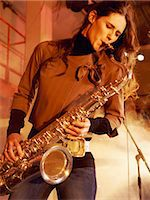 Woman Stands on a Smoky Stage Playing a Saxophone With Passion Stock Photo - Premium Royalty-Freenull, Code: 6106-07009284