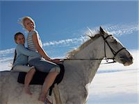 Portrait of a Woman and Her Young Daughter Sitting on a White Horse Stock Photo - Premium Royalty-Freenull, Code: 6106-07009599