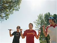 Three Young Men Holding Golf Clubs Across Their Shoulders Stock Photo - Premium Royalty-Freenull, Code: 6106-07009657