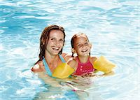 preteen swim - Smiling Mother Holding Her Daughter in a Swimming Pool Stock Photo - Premium Royalty-Freenull, Code: 6106-07009689