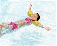 Young Girl Wearing Water Wings Floating on Water in a Swimming Pool Stock Photo - Premium Royalty-Freenull, Code: 6106-07009690