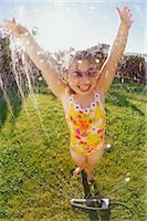 Young Girl Wearing a Swimming Costume, Being Sprayed with Water From a Garden Sprinkler Stock Photo - Premium Royalty-Freenull, Code: 6106-07009742