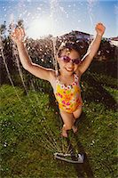 Gel Effect Shot of a Young Girl Wearing a Swimming Costume, Being Sprayed with Water From a Garden Sprinkler Stock Photo - Premium Royalty-Freenull, Code: 6106-07009743