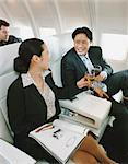 Business People Sitting in an Aircraft Enjoying a Glass of Wine
