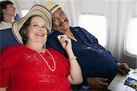 Overweight Senior Couple Sit on a Plane Sharing Cake, Crumbs on Their Clothes Stock Photo - Premium Royalty-Freenull, Code: 6106-07010095