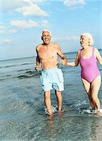 Senior Couple Walking Hand in Hand in the Surf Stock Photo - Premium Royalty-Freenull, Code: 6106-07010184