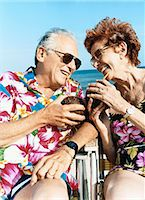 Couple Sit on Chairs Looking Face to Face and Drinking With a Straw From Coconuts Stock Photo - Premium Royalty-Freenull, Code: 6106-07010196