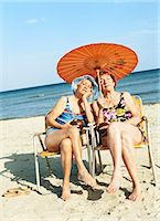 Two Bored Looking Women Sitting on Chairs Under a Parasol Stock Photo - Premium Royalty-Freenull, Code: 6106-07010200