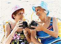 Two Senior Women Sit on the Beach Making a Toast With Coconut Cocktails Stock Photo - Premium Royalty-Freenull, Code: 6106-07010203