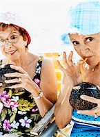 Portrait of Two Senior Women in Swimming Costumes and Sunhats Drinking Coconut Cocktails Stock Photo - Premium Royalty-Freenull, Code: 6106-07010204