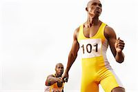 sprint - Relay Runner Passing a Baton to a Determined Looking Team Mate Stock Photo - Premium Royalty-Freenull, Code: 6106-07010231