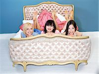 Portrait of Three Young Women Lying on an Ornate Silk Bed Stock Photo - Premium Royalty-Freenull, Code: 6106-07010345