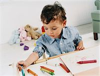 Boy Toddler Sitting Colouring With Crayons Stock Photo - Premium Royalty-Freenull, Code: 6106-07010699