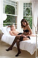 Young Woman Sitting on a Bed and Putting on Her Tights With a Man in the Background Stock Photo - Premium Royalty-Freenull, Code: 6106-07010839