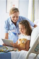 Nurse Stands by a Young Girl in a Hospital Bed, Handing Her a Notepad Stock Photo - Premium Royalty-Freenull, Code: 6106-07010898