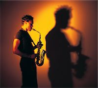 Man playing sax, throwing shadow Stock Photo - Premium Royalty-Freenull, Code: 6106-07011222