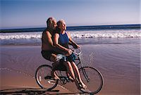 Couple riding bicycle on beach Stock Photo - Premium Royalty-Freenull, Code: 6106-07011735