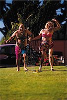 Couple running through sprinkler Stock Photo - Premium Royalty-Freenull, Code: 6106-07011747