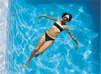 Woman floating in swimming pool Stock Photo - Premium Royalty-Freenull, Code: 6106-07012653