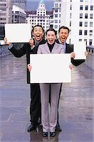 person holding sign - Three businesspeople holding blank paper Stock Photo - Premium Royalty-Freenull, Code: 6106-07013957