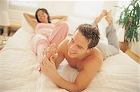 foot massage - Man Giving a Woman a Foot Massage in Bed Stock Photo - Premium Royalty-Freenull, Code: 6106-07016792