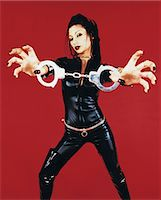 dominant woman - Portrait of a Woman Dressed in a Catsuit Holding Handcuffs Stock Photo - Premium Royalty-Freenull, Code: 6106-07018279