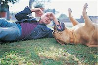 Man and Dog Playing in the Park Stock Photo - Premium Royalty-Freenull, Code: 6106-07018404