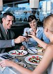 Businessman and Businesswomen in a Restaurant Lifting Their Wineglasses in Celebration