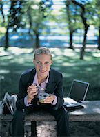 Portrait of a Businesswoman Sitting on a Bench Eating Her Lunch Stock Photo - Premium Royalty-Freenull, Code: 6106-07018744