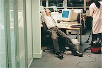 Businessman Stretching, Yawning and Working Late in the Office Stock Photo - Premium Royalty-Freenull, Code: 6106-07018826