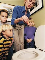 Mother Holding Dead Goldfish over Toilet as Children Watch Stock Photo - Premium Royalty-Freenull, Code: 6106-07019809