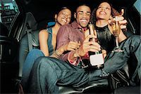 Man and Women Sitting in a Limousine Drinking Champagne Stock Photo - Premium Royalty-Freenull, Code: 6106-07020256