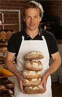 Portrait of baker in apron holding loaves of freshly baked bread Stock Photo - Premium Royalty-Freenull, Code: 6106-07021955