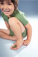 Boy (4-5) with beetle on foot, smiling Stock Photo - Premium Royalty-Freenull, Code: 6106-07022228