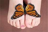 Girl (6-7) with butterfly on feet, low section, close-up Stock Photo - Premium Royalty-Freenull, Code: 6106-07022248