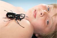 shirtless black boy - Shirtless boy (10-11) lying down with large beetle crawling on chest, portrait, close-up Stock Photo - Premium Royalty-Freenull, Code: 6106-07022259