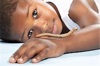 Boy (4-5) lying down with caterpillar crawling on arm, portrait, close-up Stock Photo - Premium Royalty-Freenull, Code: 6106-07022275