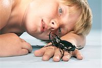 shirtless black boy - Boy (10-11) looking at large black beetle crawling on hand, close-up Stock Photo - Premium Royalty-Freenull, Code: 6106-07022279
