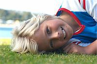 preteen long hair - Boy (12-13) lying on grass, portrait, close-up (surface level) Stock Photo - Premium Royalty-Freenull, Code: 6106-07022480