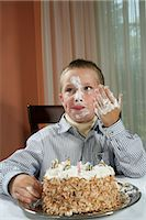 Young boy (6-7 years) with cream on face, eating birthday cake with hands, smiling Stock Photo - Premium Royalty-Freenull, Code: 6106-07022524
