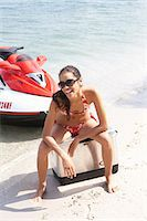 Young woman sitting on cooler by jet boat, smiling, portrait Stock Photo - Premium Royalty-Freenull, Code: 6106-07022684