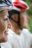 Senior couple wearing cycling helmets, close-up, profile (focus on woman in foreground) Stock Photo - Premium Royalty-Freenull, Code: 6106-07022752