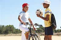 preteen touch - Two boys (11-13) talking on beach, one with bicycle, other with football Stock Photo - Premium Royalty-Freenull, Code: 6106-07022872