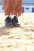 Boy (12-13) doing gymnastics on sand, low section Stock Photo - Premium Royalty-Freenull, Code: 6106-07022897