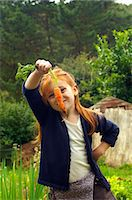 Girl (6-7) holding carrot in countryside Stock Photo - Premium Royalty-Freenull, Code: 6106-07023021