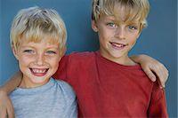 Two boys (8-10 years) embracing, portrait, studio shot Stock Photo - Premium Royalty-Freenull, Code: 6106-07023107