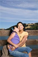 preteen kissing - Mother and daughter (10-11 years) sitting by wooden balustrade Stock Photo - Premium Royalty-Freenull, Code: 6106-07023189