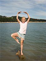preteen dancing - Girl (10-11 years) standing in ballet pose on log in lake, portrait Stock Photo - Premium Royalty-Freenull, Code: 6106-07023196